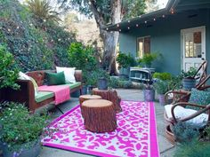 A bold, colorful area rug can transform a boring outdoor space into a lively area for entertaining. Designer Emily Henderson created this bohemian outdoor room with a patterned area rug, stumps-turned-cocktail-tables and basic string lights.