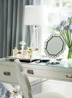 Inside Suzanne Kaslers Stunningly Serene Atlanta Home -- Feminine, classic style with a mirror top vanity, perfume tray and fresh flowers. For more sophisticated traditional interior design ideas, see the full home tour on our Style Guide!
