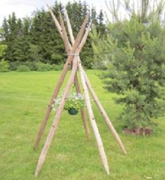 Use 5 old hay poles to make a stand outside. Tie them together with a chain. Drop the end inside, so you can hang the flowers from it.