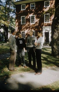 A group of Bowdoin College men stand around talking outside a dormitory. One of them is wearing a big B letter sweater and gray slacks.