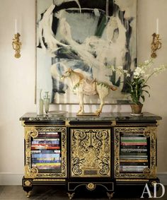 Interesting modern painting mixed with  asian art (antique cabinet) ceramic horse with other periods.  What makes it work??? Perhaps the painting says something about the potential movement of the horse.  How can contrasting cream colors (horse & Painting) somehow complement jvj