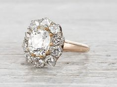 Vintage Victorian cluster ring made in 18k yellow gold and centered with an approximately 1.08 carat EGL certified old European cut diamond with I-J color and SI1 clarity. Surrounded by 10 old Europea