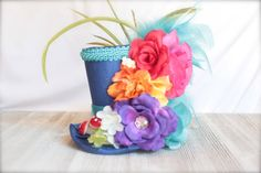 This gorgeous top hat is made with an blue textured fabric. For an even more glamorous look this hat has been finished off with pearls, feathers, rosettes, and lil mushrooms embellishments. This mini top hat is made on an elastic band which is cut to size so please indicate what size you would like in the notes to seller at check out.  Headband sizes are as follows:  Extra Small (Preemies or extra small head -12 ) Small (Newborn to 6 Months -13) Medium (6 to 18 months - 15) Large (18 Months…