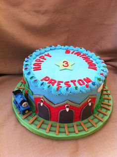 Thomas The Train - 10 inch cake frosted in buttercream, accents are fondant. Thomas is just a toy. TFL