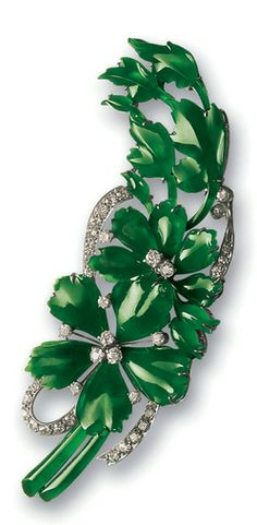JADEITE AND DIAMOND BROOCH Carved as a flower bouquet set with twenty translucent emerald green jadeite plaques, decorated by ribbon scrolls set with old mine-cut diamonds, mounted in white metal. Jadeite plaques approximately 9.51 x 3.21 x 2.30 to 16.66 x 11.36 x 3.21 mm.
