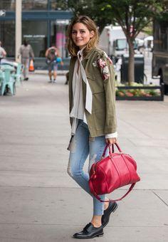 Le sigue muy de cerca Olivia Palermo con este look de calle con parka de flores de Topshop, camisa blanca anudada al cuello, vaqueros pitillo, zapatos masculinos y bolso rojo.