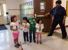 Why Might My Child With Low Vision Need Orientation and Mobility Training? (Image: four children, two with canes, two without, smiling as their orientation and mobility instructor holds the door open for them)