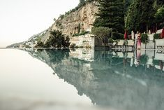 couple are hugging in front of the swimming pool that reflect the amalfi coast