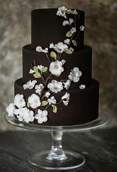 A Chocolate Wedding Cake With White Flowers. Rich, chocolaty browns conjure up the best of winter. Ana Parzych Cakes whipped up a cake in the shade that featured wedding-worthy white flowers. See more brown wedding cakes. Beautiful Wedding Cakes, Gorgeous Cakes, Pretty Cakes, Amazing Cakes, Brown Wedding Cakes, Black And White Wedding Cake, Chocolate Wedding Cakes, Chocolate Cake, White Chocolate