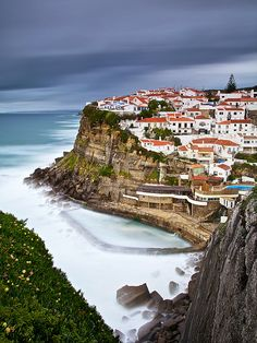 Azenhas do Mar, Portugal - notice the 'pool' next to the cliff;  this small village is situated in a picturesque valley;  it has one of the most interesting beaches of Sintra, with one swimming pool dug out of the rock;  photo by CResende, via Flickr