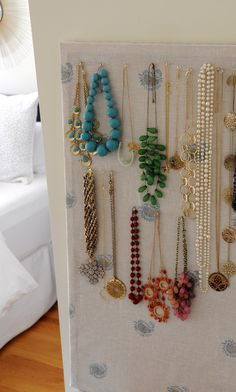 DIY Necklace Holder:    To make:     Cork-board  Fabric  Staple Gun      Cut fabric to fit cork board (iron if necessary), wrap board with fabric and staple away.  You could also add a ribbon border, nailhead trim, the options are limitless!