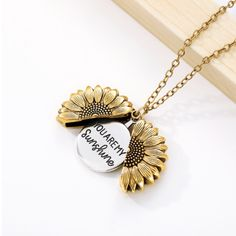 "Sunflowers are symbols of happiness, unwavering faith and unconditional love. This beautiful sunflower necklace opens up to reveal the engraved words ""You Are My Sunshine"". It's the perfect gift for a loved one, showing them just how much you adore them and appreciate them.  Metal brass chain and alloy 48 cm + 5 cm wit"