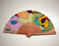 To create this beautiful piece, first I painted the silk and then a hand fan artisan mounted it on a structure of Pear Tree wood.  This is a folding fan