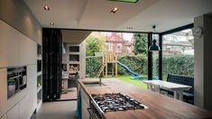 Vind afbeeldingen van moderne Keuken: Aanbouw en renovatie van 2-onder-1-kapper met ruime woonkeuken met kookeiland, gietvloer en luxe aluminium vouwschuifpui. Ontdek de mooiste foto's & inspiratie en creëer uw droomhuis.
