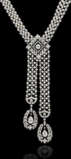 A belle époque pearl and diamond sautoir, J.E. Caldwell, circa 1910,  the woven seed pearl necklace centering a lozenge-shaped panel of old European-cut diamonds in a foliate motif suspending an asymmetrical pendant each with terminals of pear-shaped diamonds within diamond foliate borders; signed J.E.C. & Co, no. F3699; mounted in platinum; length: 18in. Via Bonhams.