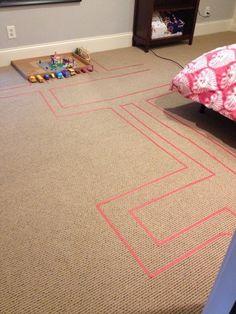 Coloque fita colorida no carpete para fazer pistas para os carrinhos de brinquedo de seu filho.