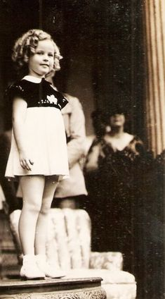 Shirley Temple facing the enormous crowds in Hawaii, 1935. Her mother looks on in the background.