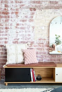 Light Lab, studio créatif Californien. Meuble de rangement en bois style épuré, coussin ethnique, mur de brique. / Light Lab, creative studio Californian. wooden storage cabinet minimalist style, ethnic cushion brick wall.