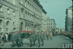 A March of Wehrmacht troops through the streets of Berlin with Hitler Youth boys watching on with awe. In the perception of the youth that were living in the Third Reich, they saw the most desirable and glorious life for a man was being a soldier.