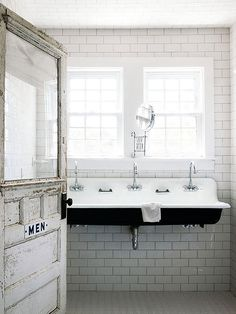 This way-cool lavatory accessed by a salvaged exterior door accommodates multiple hand-washers at the wall-mount trough sink. White subway tiles run from floor to ceiling to establish country character and protect the walls from water and soap splatters.