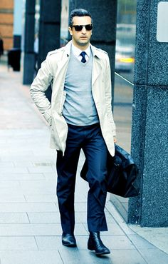 Cream colored trench, Grey vneck jumper, navy trousers, and black Chelsea boots