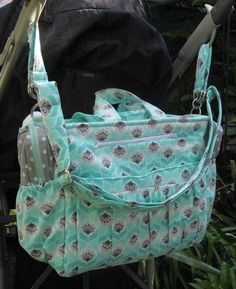 """Diaper Bag PDF Pattern  Finished Size: 14"""" wide x 11"""" high x 5 1/4"""" deep Skill Level: Intermediate  The On the Go Diaper Bag features a roomy inside plus multiple interior and exterior pockets of varying sizes to hold all of baby's necessities. Pattern includes yardage amounts and instructions to create diaper bag, changing pad, stroller straps and two insulated bottle bags. This fresh new bag has lots of fabulous features to make your day on the town easier with baby, and is perfect for..."""