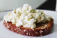 A hearty clean eating lunch of egg salad made with olive oil mayo and greek yogurt over whole wheat toast.