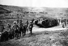 ritish Mark I tank, apparently painted in camouflage, flanked by infantry soldiers, mules and horses. (National Library of Scotland)