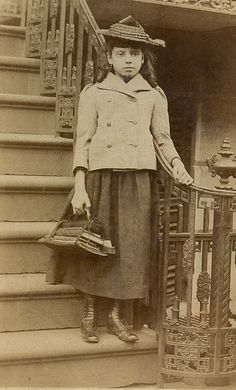 Vintage Photo (circa unknown): Teen school girl heads off to school in the city carrying her books. Note that this was long before the days of backpacks and her books are bound together with leather straps, as was typical of the time period.