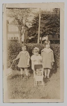 Vintage photo of three little girls play with an umbrella and a doll in a doll buggy circa 1925.