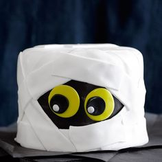 """An eerie-sistible Halloween dessert featuring five layers of decadent chocolate cake, filled with velvety chocolate cream cheese frosting. The creation is covered with fondant """"bandages""""."""