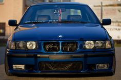 Front end of an Avus Blue BMW e36 sedan. Agressive, not?