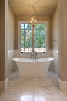 Gorgeous master bath alcove features top half of walls painted warm beige and lower half of walls clad in white marble subway tiles finished with marble pencil rails framing window over a freestanding tub paired with floor-mount vintage tub filler illuminated by a Currey & Co Bella lUna Chandelier.