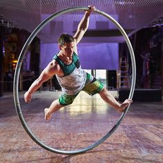 Coleton Stinson improvises on the Cyr wheel, spinning while holding on with one foot and one hand. @nicoletsong writes spinning in a Cyr wheel at Emerald City Trapeze Arts is a great workout, but there will be falls. ( by Benjamin Benschneider / The Seattle Times)  Read the story by going to the link in our profile. #exercise #cyr #wheel #workout