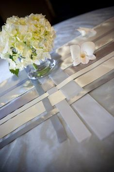 Ribbon Table Runners — The white, silver, and charcoal satin ribbons on this table from Wedding Wire are trés chic. The ribbon table runner is simple and subtle, yet stunning. #ribbon #tablerunners #diy