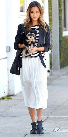 Jamie Chung wearing a sheer white midi-length skirt with a striped tank by twenty, a leather moto-style jacket, and cut-out Sol Sana booties.
