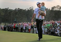 Bubba Watson holds his 2-year-old son, Caleb, as he leaves the 18th hole after winning the Masters