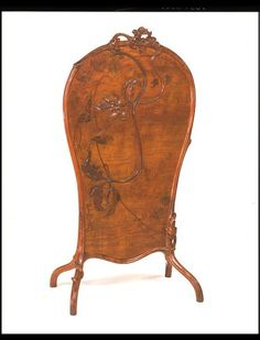 Emile Galle's love for plants is expressed in this beautifully carved fire screen made of Ash in 1900 France.  Starting his career as a glassware designer and slowly moving to furniture-making this piece displays his talent of producing elegant pieces.   It Features the characteristics of art nouveau style with the flowing lines and marquetry decoration of various woods along with carvings of fronds and leaves.