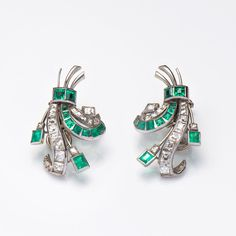 A pair of emerald and diamond earrings, of stylised spray design and set throughout with calibre cut diamonds and emeralds. 18ct white gold.