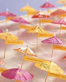 These cheerfully colored umbrellas sporting seating assignments dot miniature sand dunes at the entrance to a summer reception.