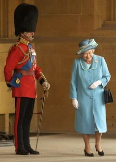The Queen breaking into laughter as She passes Her husband, the Duke of Edinburgh, standing outside the Buckingham Palace
