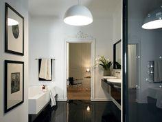 Douche moderne avec pomme de douche design et jet de massage intégré. Carrelage en pierres noires brillantes. La baignoire a été encastré parfaitement dans le mur pour donner une impression de tranquillité. Les lavabos sont soutenus par un meuble
