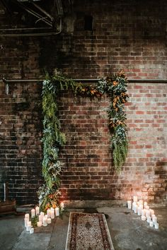 foliage garland wedding backdrop on exposed brick wall