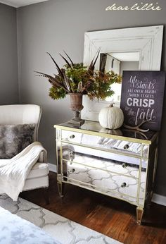 A neutral pumpkin, fall quote artwork, and bouquet of tree branches and turkey feathers update this guest room for autumn.