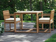 une table et deux chaises en teck dans le jardin