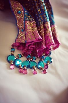 love the baubles on the edges of this scarf, have a bracelet kit from 7 gypsies with word tiles...think they would look good hanging on a scarf like this... maybe.