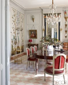 The grand dining room of a manor house in the Bordeaux wine region features 18th-century painted chinoiserie panels, an antique mahogany table, and gilded-bronze candelabras.   - ELLEDecor.com