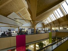 Open plan office at first floor level under north light saw tooth roof with atrium providing natural lighting and visual connection to Community Hub below