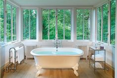 Detta romantiska badrum finns på hotellet Lime Wood, Hampshire, England.  I think I just like the idea that an entire room could be windows and a claw foot tub!