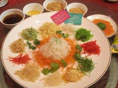 Never heard of Yee Sang before? This article explores the concept and meaning behind this traditional Chinese New Year dish. Chinese New Year Dishes, Traditional Chinese, Hummus, Singing, Curry, Ethnic Recipes, Restaurants, China, Food